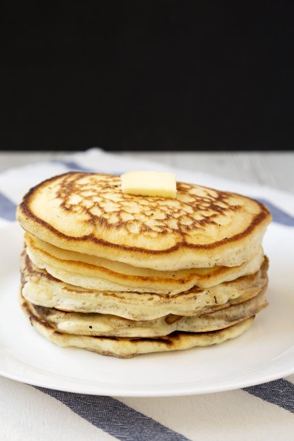 Hemlagade pannkakor med smör på en vit platta, sidosikt N?rbild arkivbild