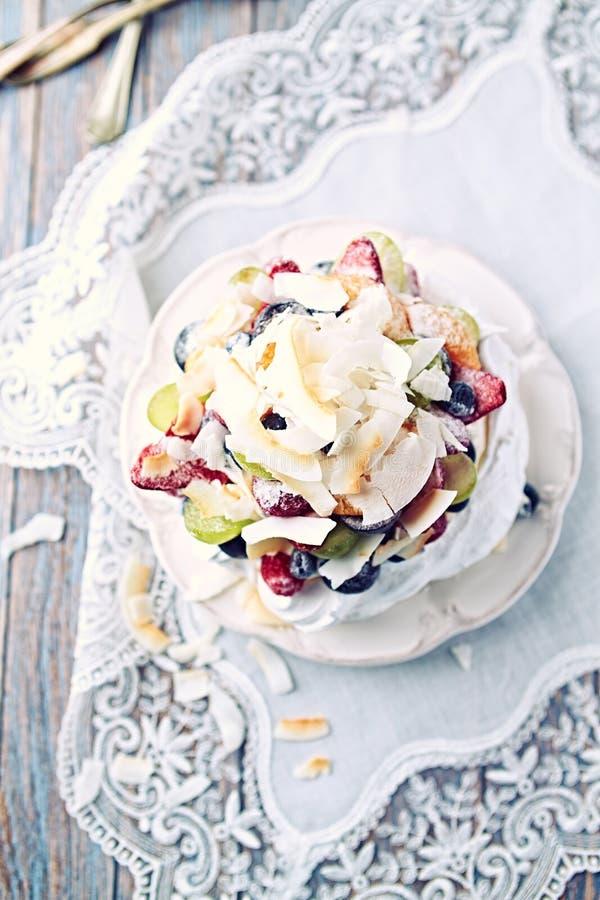 Hemlagade Pavlova med nya frukter och kokosnöten; Baka ihop med blåbär, jordgubbar, druvor, hallon och kokosnöten royaltyfri bild