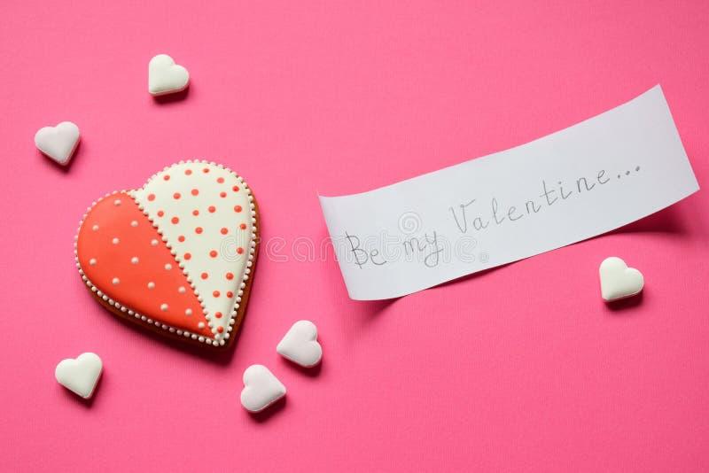 Hemlagade pepparkakahjärtor och papper med text att vara min valentin Kakahjärtor på rosa bakgrund Ätlig nolla för valentindaggåv royaltyfri foto