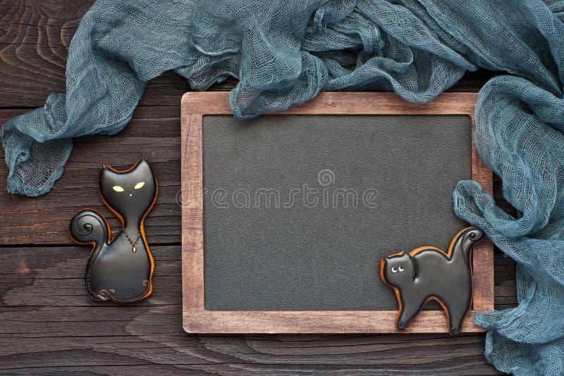 Hemlagade pepparkakakakor i form av svarta katter H?stbakgrund, halloween feriebegrepp arkivfoto