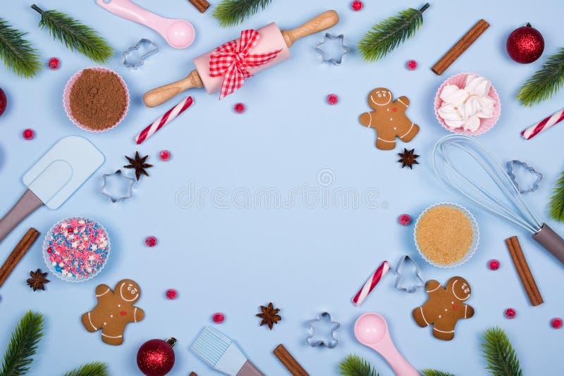 Hemlagade pepparkakakakor med ingredienser för julbakning och köksgeråd på blå pastellfärgad bakgrund, royaltyfri fotografi