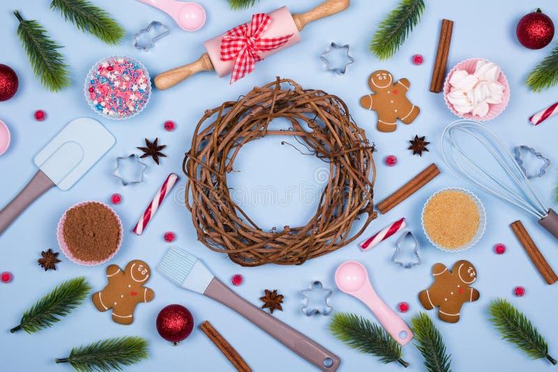 Hemlagade pepparkakakakor med ingredienser för julbakning och köksgeråd på blå pastellfärgad bakgrund, royaltyfria foton