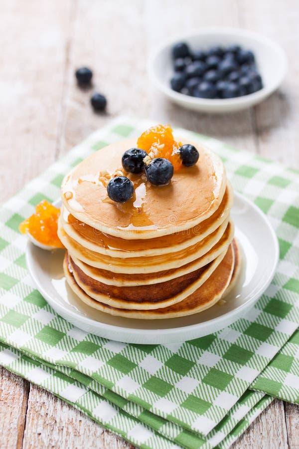 Hemlagade söta pannkakor med blåbär, fruktdriftstopp och honung royaltyfri bild