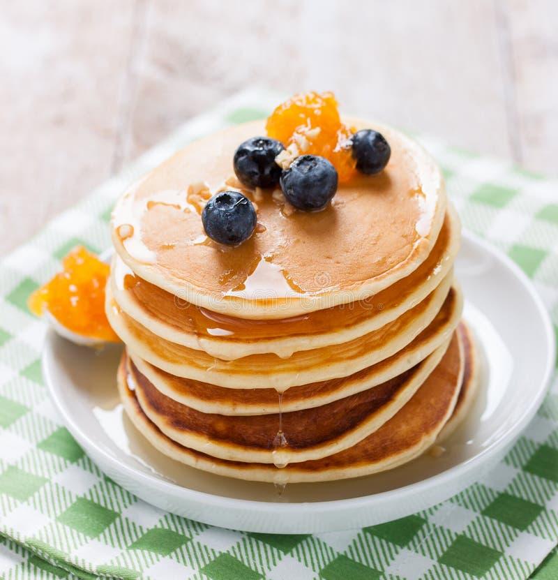 Hemlagade söta pannkakor med blåbär, fruktdriftstopp och honung royaltyfria foton