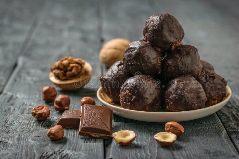Hemlagade sötsaker gjorde från muttrar, torkade frukter, choklad och honung på en platta på en svart tabell royaltyfri fotografi