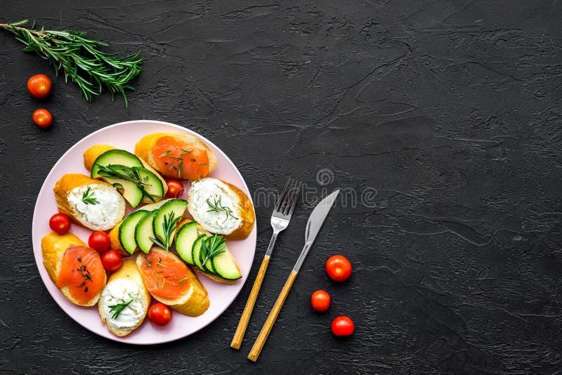 Hemlagade smörgåsar med den franska bagetten, laxen, ost och grönsaken på svart modell för bästa sikt för bakgrund arkivfoton