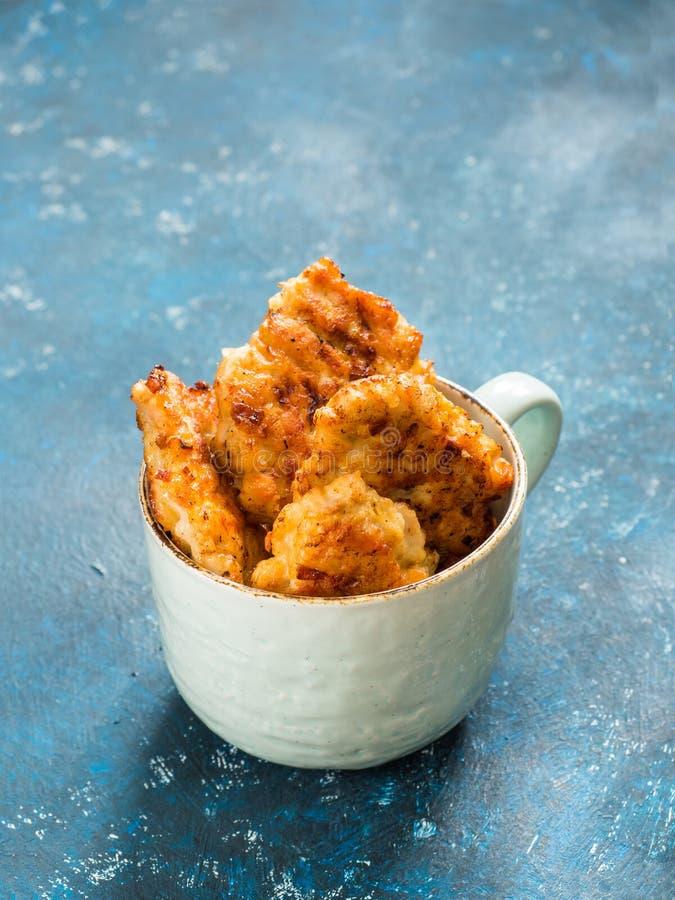 Hemlagade stekt kycklingkotletter, filéklumpar i keramiskt rånar på blå bakgrund begreppet bantar sund mat arkivfoto