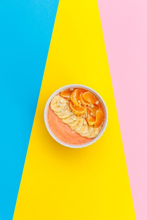 Hemlagade yoghurttangerin och bananer på en platta på kulöra bakgrunder r Top besk?dar royaltyfri foto