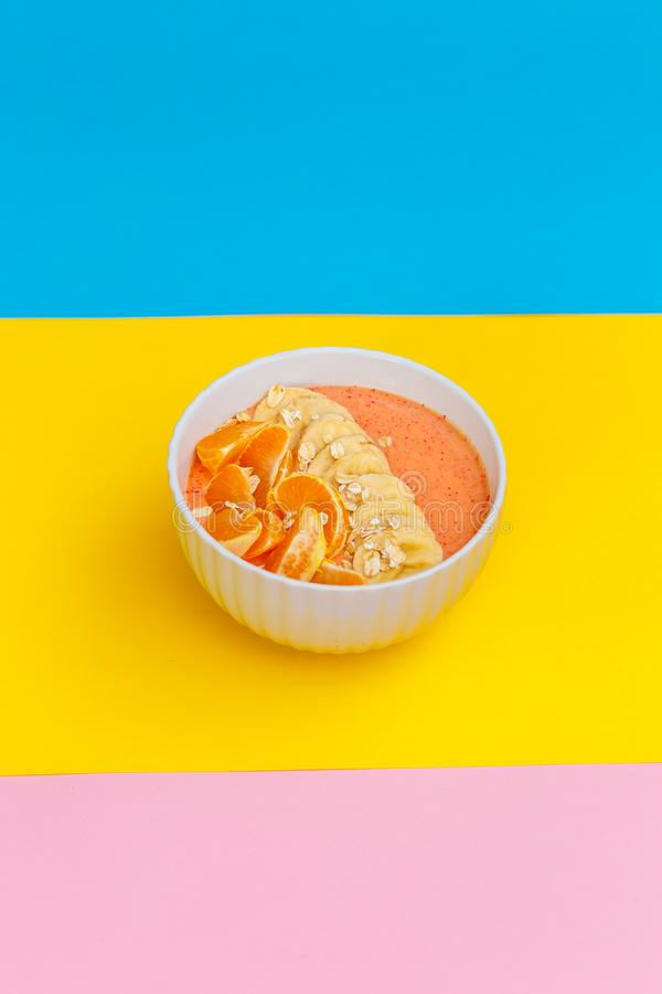 Hemlagade yoghurttangerin och bananer p? en platta p? kul?ra bakgrunder r Top besk?dar arkivfoton