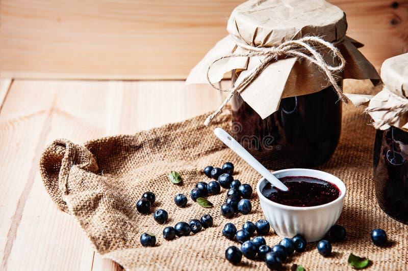 Hemlagat blåbärdriftstopp i en krus och nya blåbär på tabellen fotografering för bildbyråer