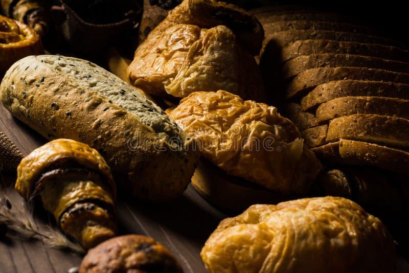 Hemlagat bröd består av skivan och bullen, franskbröd, muffin och giffel som förläggas på den bruna trätabellen, för bruk som aff arkivfoton