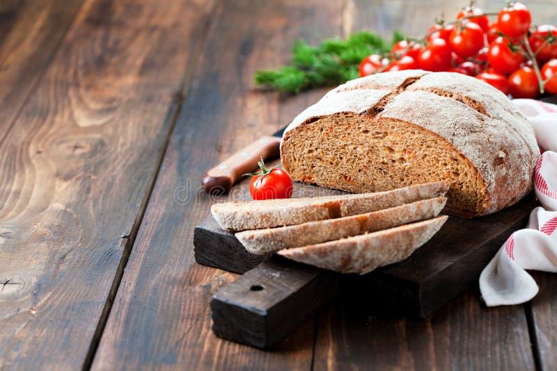 Hemlagat bröd för helt vete med sundried tomater och örter royaltyfri foto