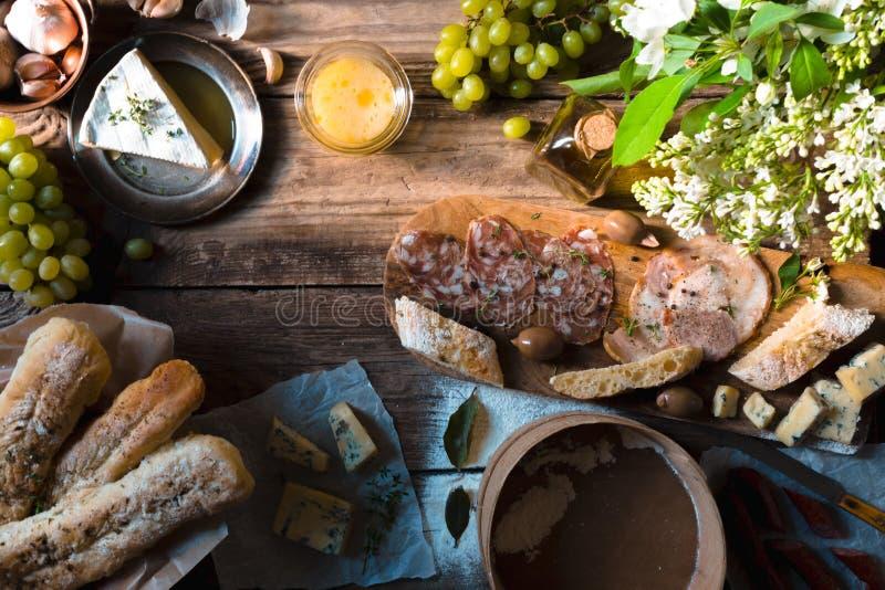Hemlagat bröd, ost, korv och bukett av lilor på tabellen arkivfoto