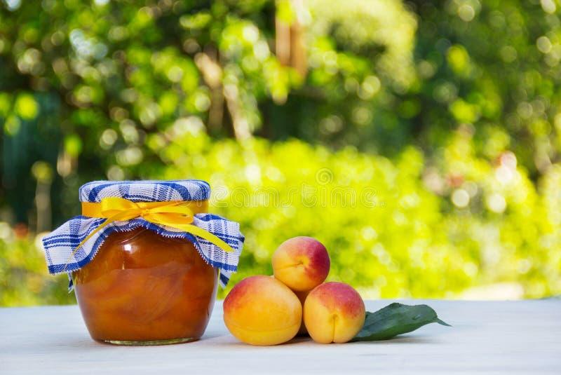 Hemlagat driftstopp på en grön naturlig bakgrund En krus av hem- aprikosdriftstopp och nya aprikors på en vit tabell royaltyfri foto