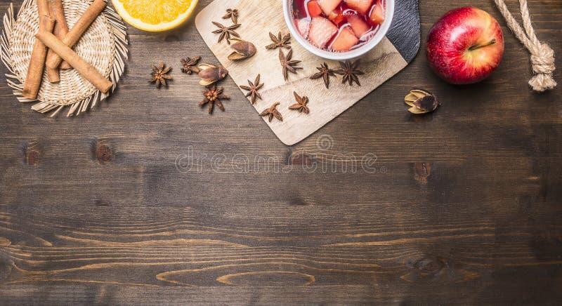 Hemlagat funderat vin med äpplet, apelsinen, kanel, kryddnejlikor och andra ingredienser har lagts ut omkring på trälantlig backg royaltyfria foton