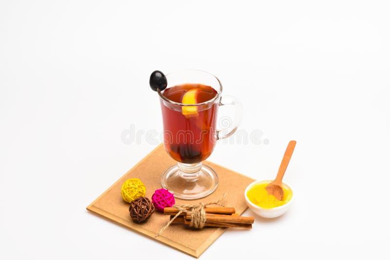Hemlagat funderat vinbegrepp Exponeringsglas med funderat vin eller varmt te med druvan, kanel och honung på vit bakgrund arkivbilder