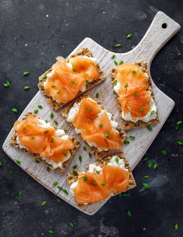 Hemlagat knäckebrödrostat bröd med den rökte laxen och mjuka chees, gräslökar på det vita brädet royaltyfria bilder