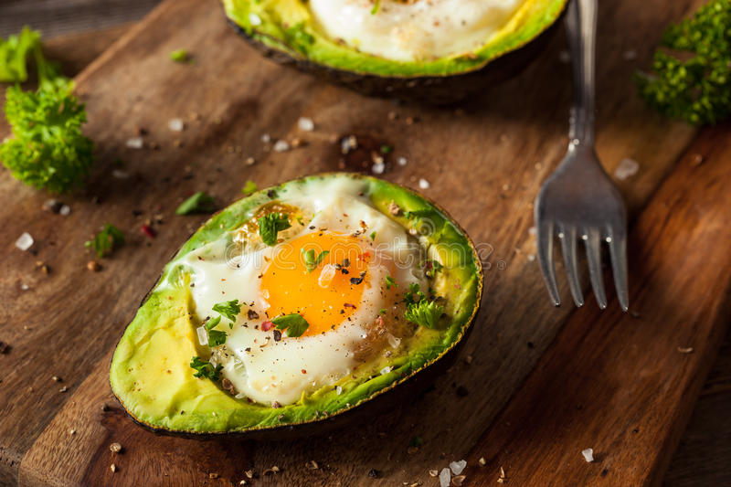 Hemlagat organiskt ägg som bakas i avokado royaltyfri fotografi