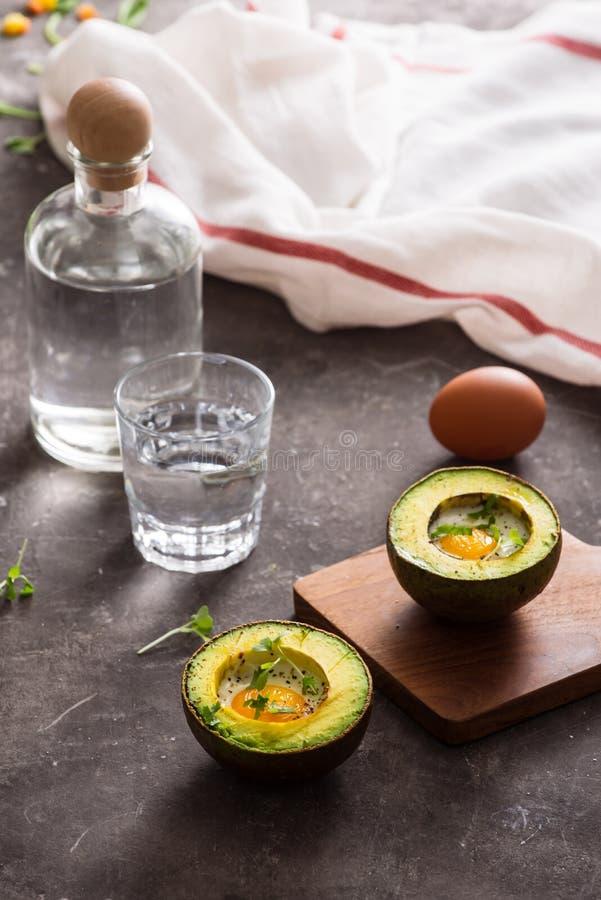 Hemlagat organiskt ägg som bakas i avokado med salt och peppar arkivfoton