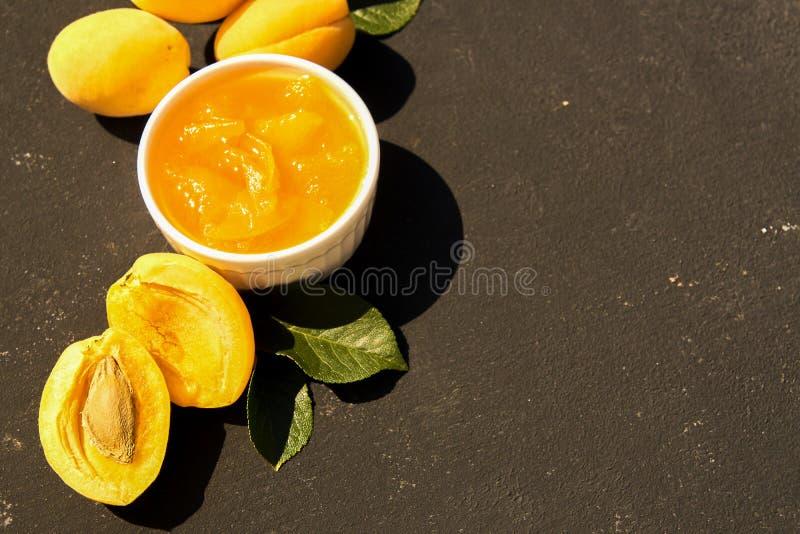 Hemlagat organiskt aprikosdriftstopp i den vita bunken och mogna aprikors på svart bakgrund H?rd lampa royaltyfri bild