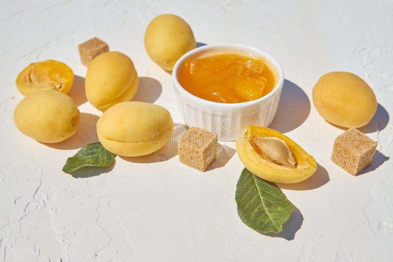 Hemlagat organiskt aprikosdriftstopp och mogna aprikors och farin på vit bakgrund royaltyfria bilder