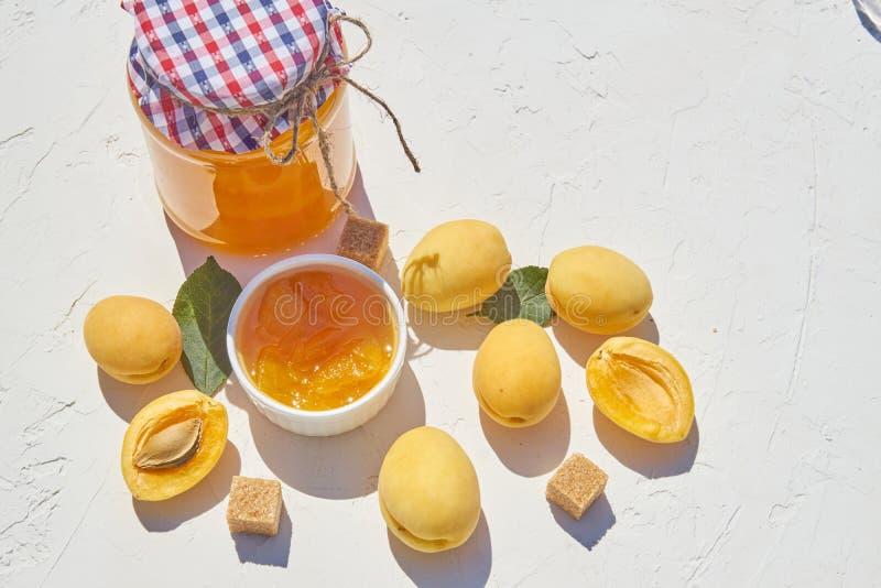 Hemlagat organiskt aprikosdriftstopp och mogna aprikors och farin på vit bakgrund arkivfoto