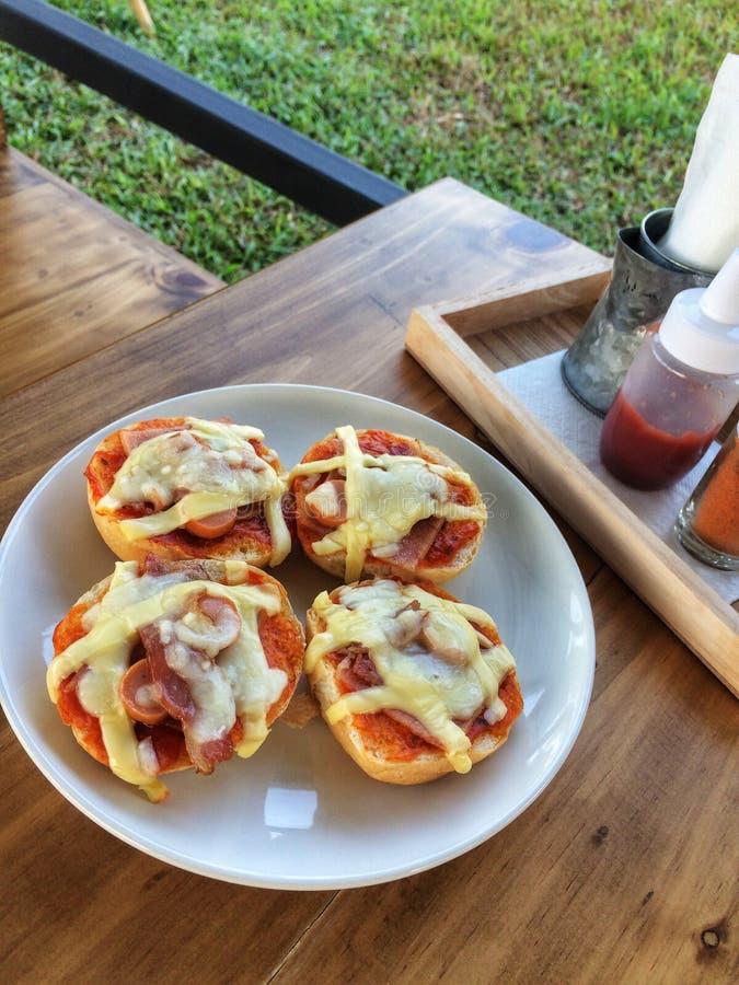 Hemlagat rostat bröd som överträffas med bacon, ägget och ost i den vita maträtten royaltyfri fotografi