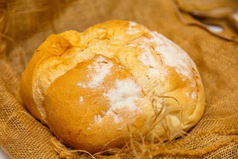 Hemlagat runt bröd från vetemjöl ligger på den grova torkduken royaltyfri foto
