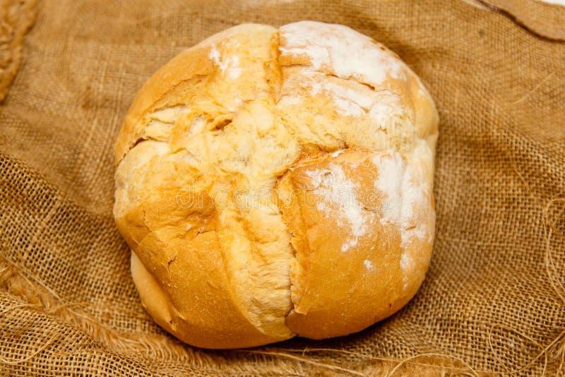 Hemlagat runt bröd från vetemjöl ligger på den grova torkduken royaltyfria foton