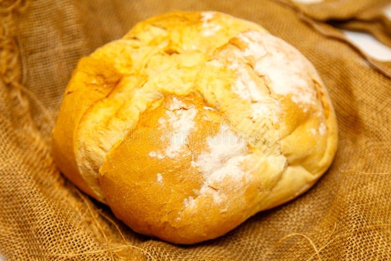 Hemlagat runt bröd från vetemjöl ligger på den grova torkduken fotografering för bildbyråer