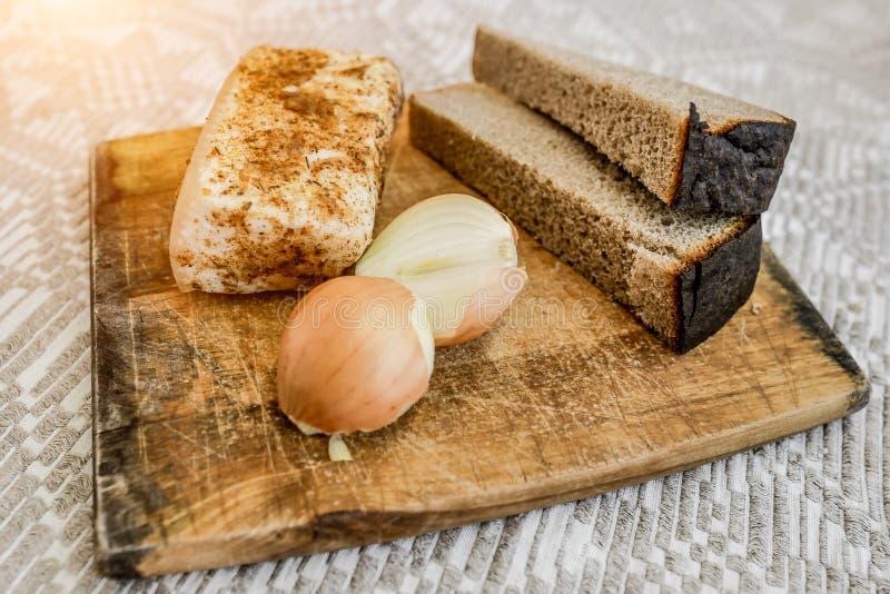 Hemlagat späcka, bröd och lökar på skärbrädan Nationell mat arkivbild