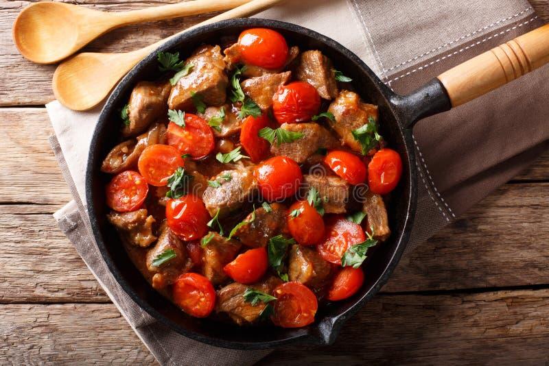 Hemlagat steknötkött i sås med körsbärsröda tomater och gräsplanclo arkivfoto