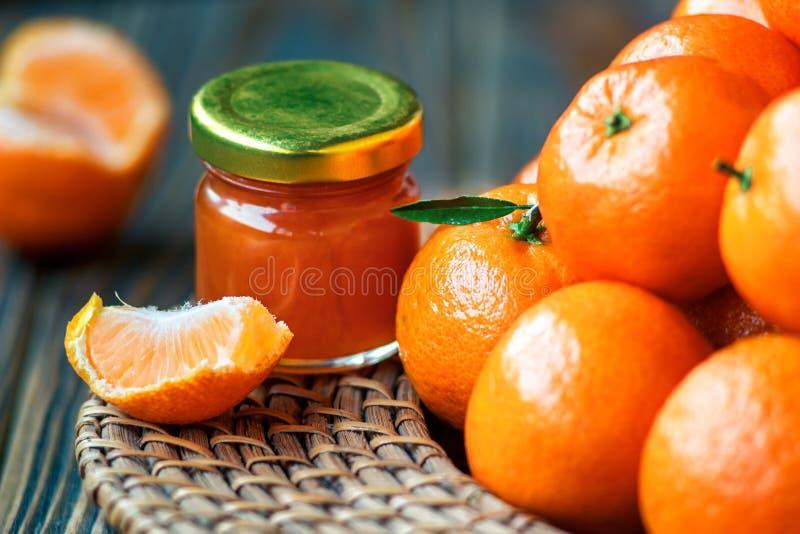 Hemlagat tangerindriftstopp i den glass kruset med frukt omkring på en trätabell fotografering för bildbyråer