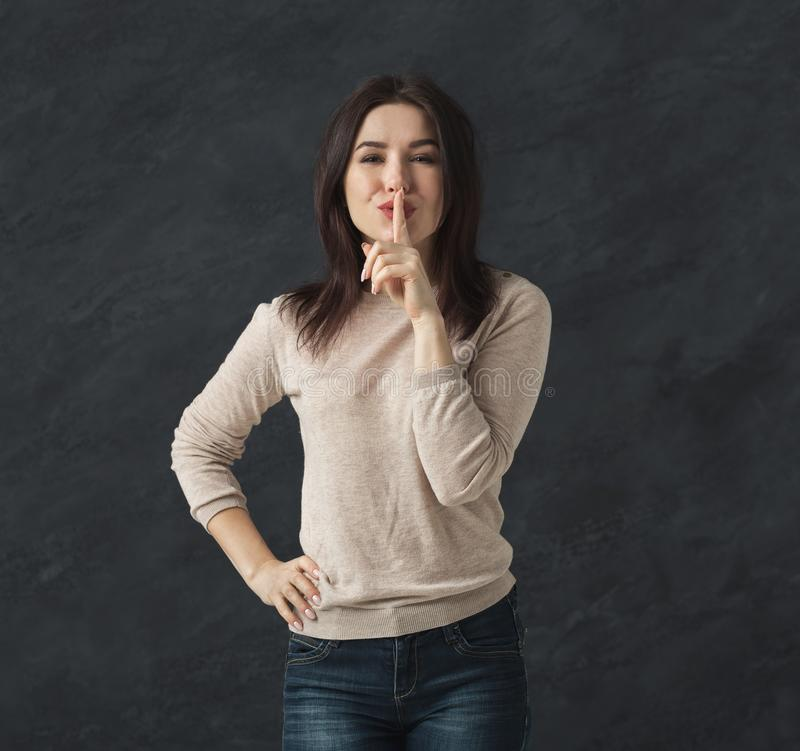 hemlighet Hyssjar det satta fingret för den unga kvinnan på kanter, tecknet royaltyfri fotografi