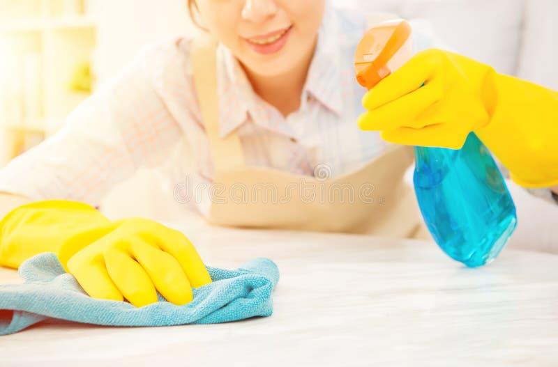 Hemmafru i gula handskar som gör ren tabellen royaltyfri foto