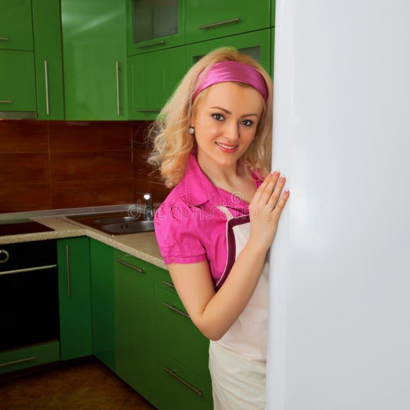 Hemmafru i kök med kylen royaltyfri bild