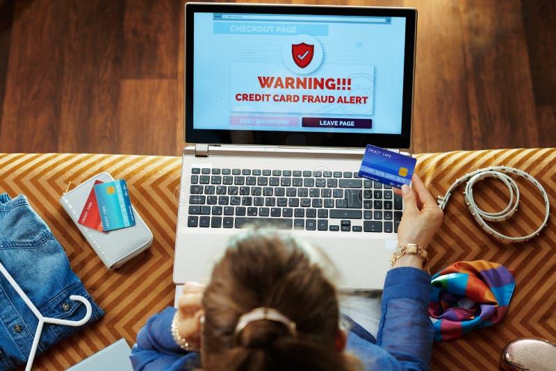 Hemmafru med kreditkorten som gör säker online-shopping royaltyfri bild