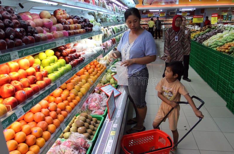 Hemmafru och hennes sonshopping på en av supermarken i staden av soloen, centrala Java Indonesia de köper frukt och andra lodisar arkivfoton