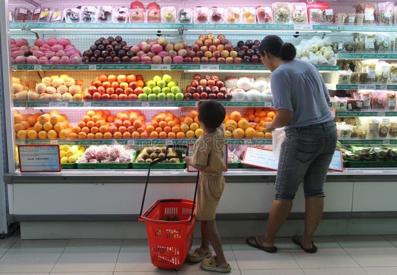 Hemmafru och hennes sonshopping på en av supermarken i staden av soloen, centrala Java Indonesia de köper frukt och andra lodisar royaltyfri foto