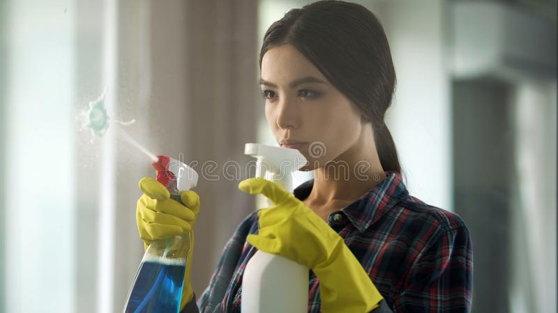 Hemmafru som besprutar olika fönsterrengöringsmedel på exponeringsglas som kommer med huset till beställning arkivbild