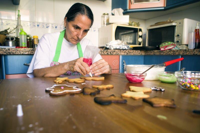 Hemmafru som förbereder julkakor royaltyfri foto