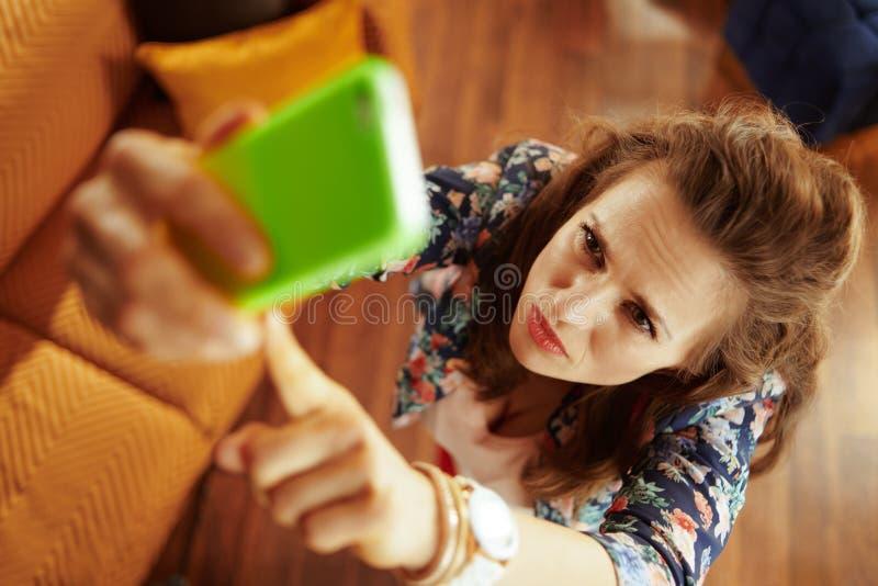 Hemmafru som försöker att få den bättre wifisignalen på smartphonen fotografering för bildbyråer
