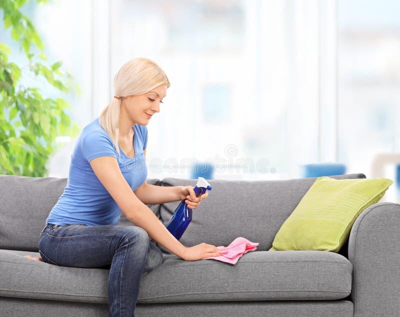 Hemmafru som gör ren en soffa med en trasa royaltyfria foton