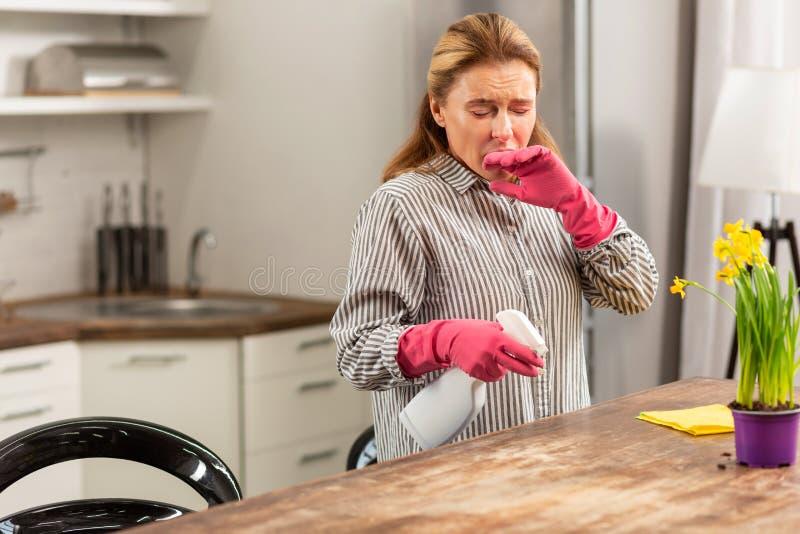 Hemmafru som gör ren köket som nyser, medan ha allergi arkivbilder