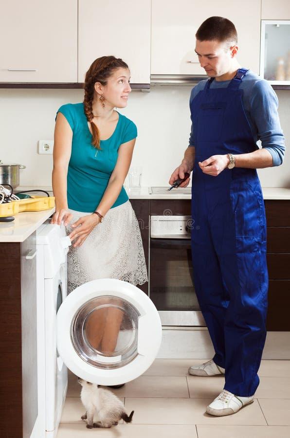 Hemmafru som håller ögonen på som teknikern som reparerar tvagningmaskinen royaltyfri bild
