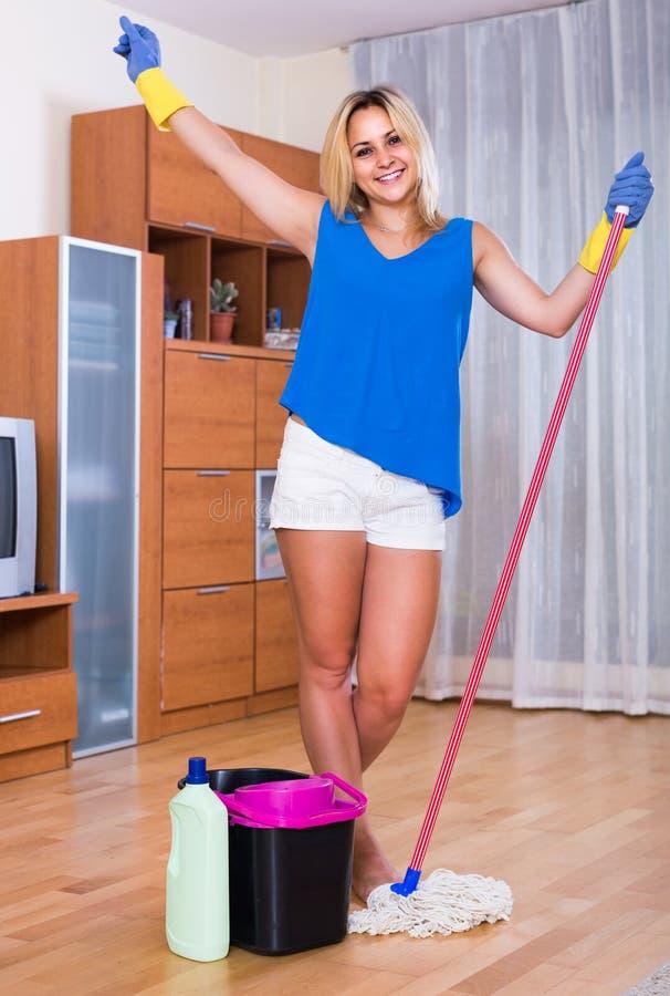 Hemmafru som ler och gör golvet som inomhus gör ren royaltyfria foton