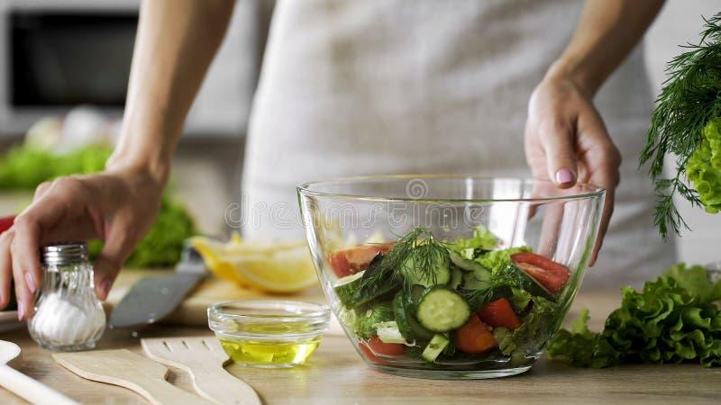 Hemmafru som tar saltkaret på tabellen för att krydda lunchsallad, smaklig aptitretare royaltyfria foton
