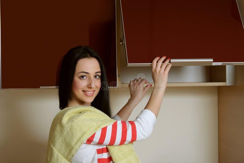 Hemmafrubrunetten i hem- kläderkökskåp öppnar royaltyfri foto