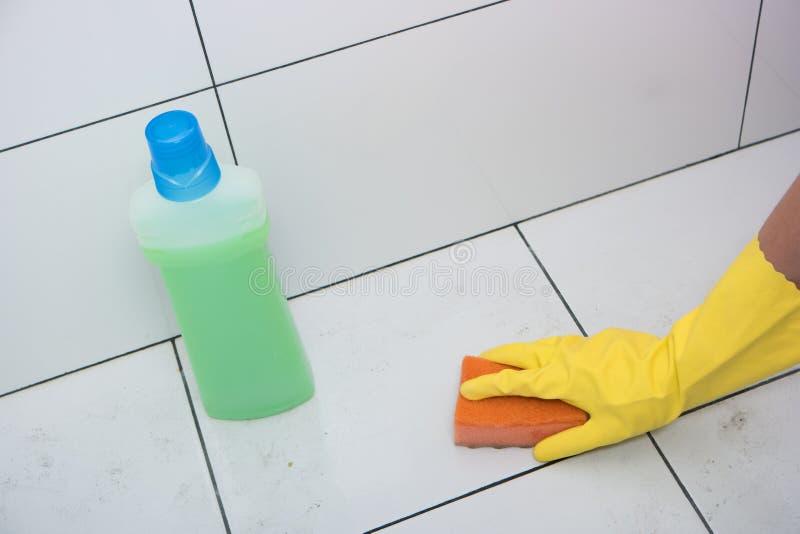 Hemmafruhand i en gul rubber handske med svampen royaltyfria foton