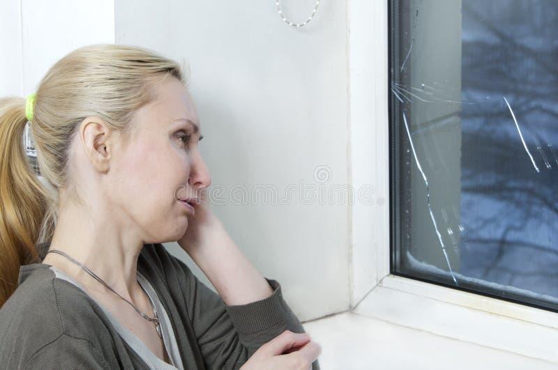 Hemmafrun gråter, det dåliga kvalitets- fönstret har brustit på grund av kallt väder arkivfoton